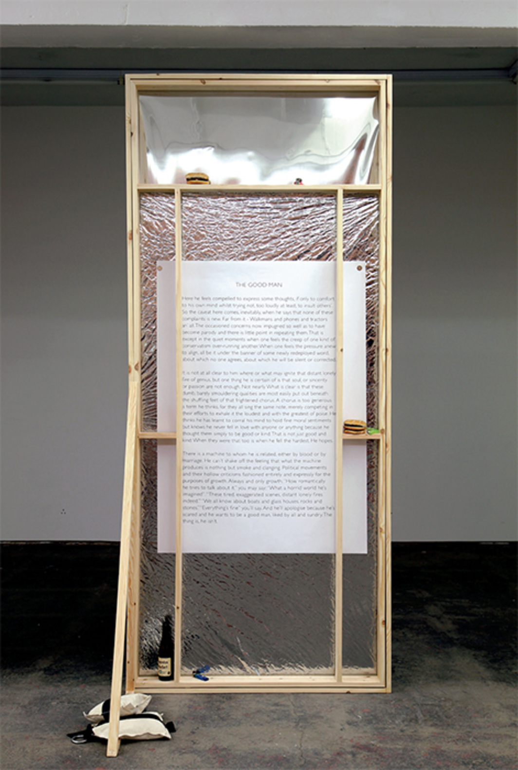 "David Raymond Conroy, Broadway Flat (The Good Man), 2015, wood, privacy film, magnets, sandbags, wide-format print, plotter print, dehydrated Big Mac, dehydrated Quarter Pounder, lighters, Trappistes Rochefort bottle, 94 1/2 × 35 3/8 × 29 1/2""."