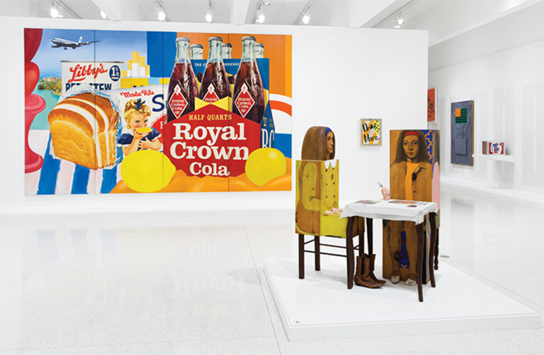 "View of ""International Pop,"" 2015, Walker Art Center, Minneapolis. Foreground: Marisol, Dinner Date, 1963. Background, from left: Tom Wesselmann, Still Life #35, 1963; Ushio Shinohara, Drink More, 1964; Jasper Johns, Flags, 1965; Paul Thek, Meat Piece with Warhol Brillo Box, 1965. Photo: Gene Pittman."