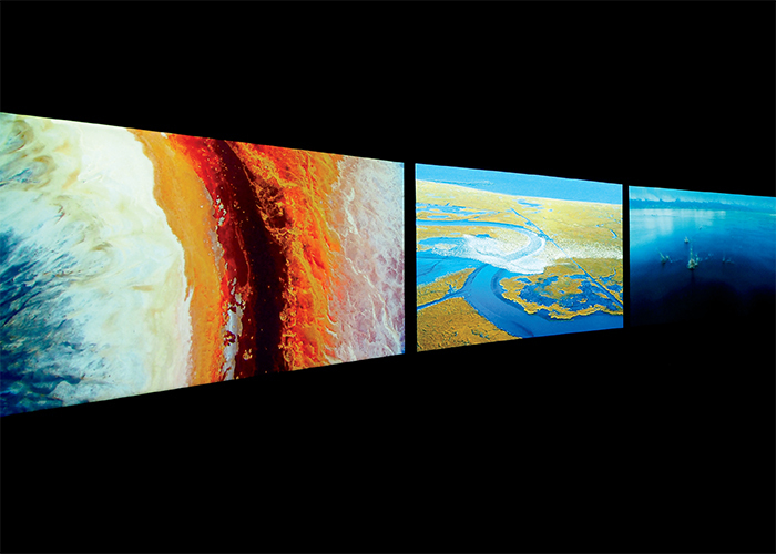 John Akomfrah, Vertigo Sea, 2015, three-channel HD video, color, sound, 48 minutes. Installation view, Central Pavilion, Venice, 2015. From the 56th Venice Biennale. Photo: Cristiano Corte. © Smoking Dogs Films.