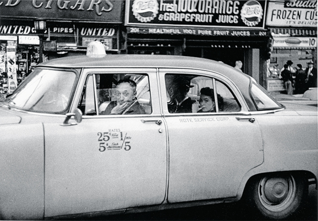 "Diane Arbus, Taxicab driver at the wheel with two passengers, N.Y.C., 1956, gelatin silver print, 6 1/8 × 8 7/8"". © The Estate of Diane Arbus, LLC."