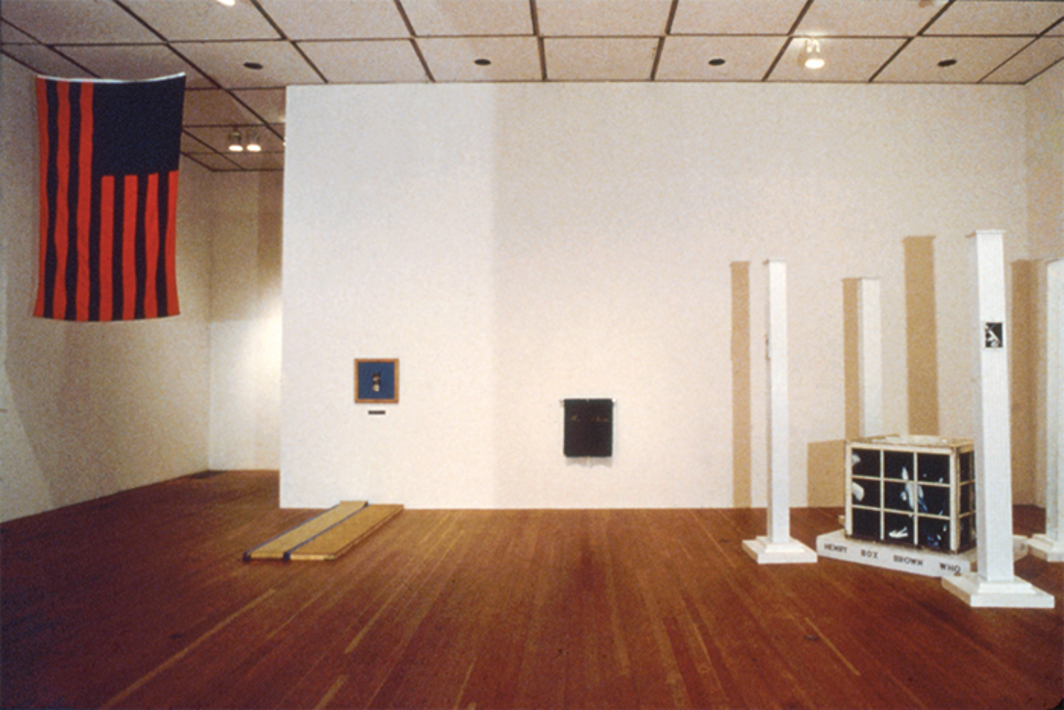 "View of ""The Theater of Refusal: Black Art and Mainstream Criticism,"" 1993, Fine Arts Gallery, University of California, Irvine. From left: David Hammons, African American Flag, 1990; Renée Green, Blue Skies, 1990; Gary Simmons, Us & Them, 1990; Pat Ward Williams, 32 Hours in a Box . . . and Still Counting, 1988. Photo: Catherine Opie."