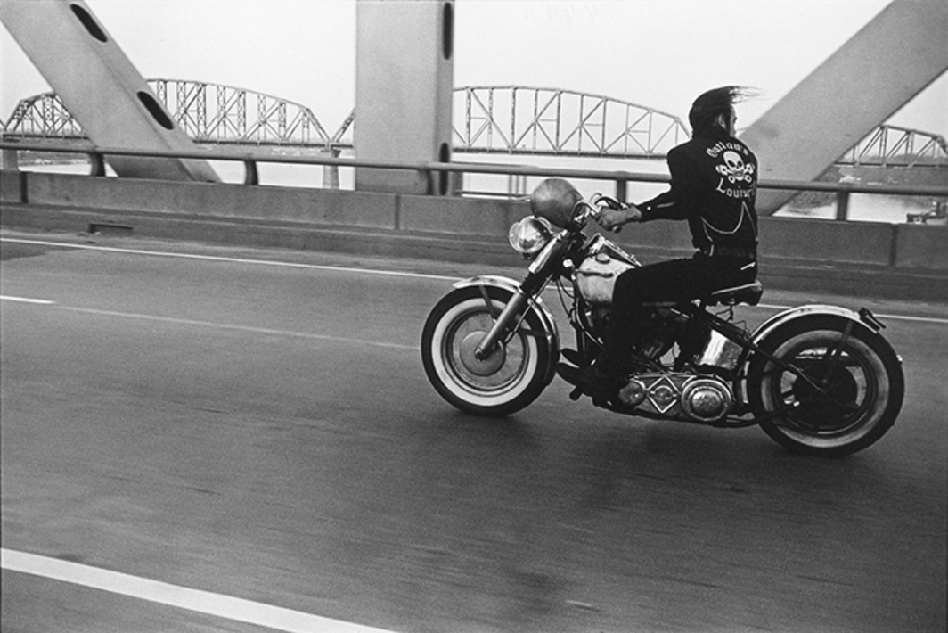 "Danny Lyon, Crossing the Ohio River, Louisville, 1966, gelatin silver print, 8 × 12 1/2"". From the series ""The Bikeriders,"" 1962–66. © Danny Lyon/Magnum Photos."