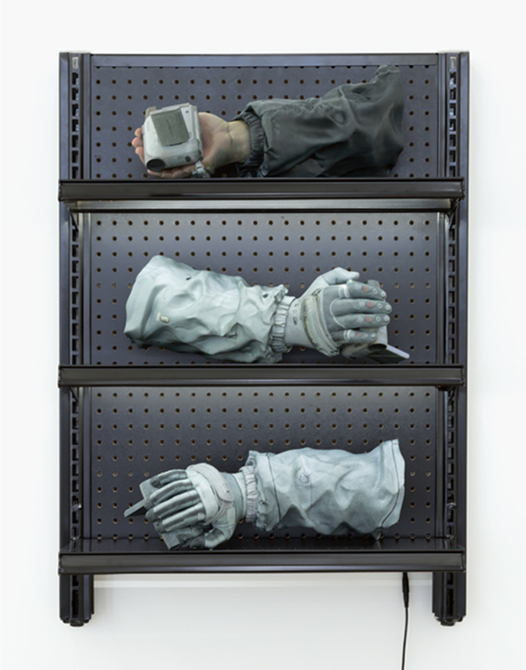 "Josh Kline, RAID Drives, 2015–16, plaster, ink-jet ink, cyanoacrylate, handcuffs, commercial shelving, LED lights, 37 × 27 1/2 × 15"". From ""The Politics of Portraiture."""