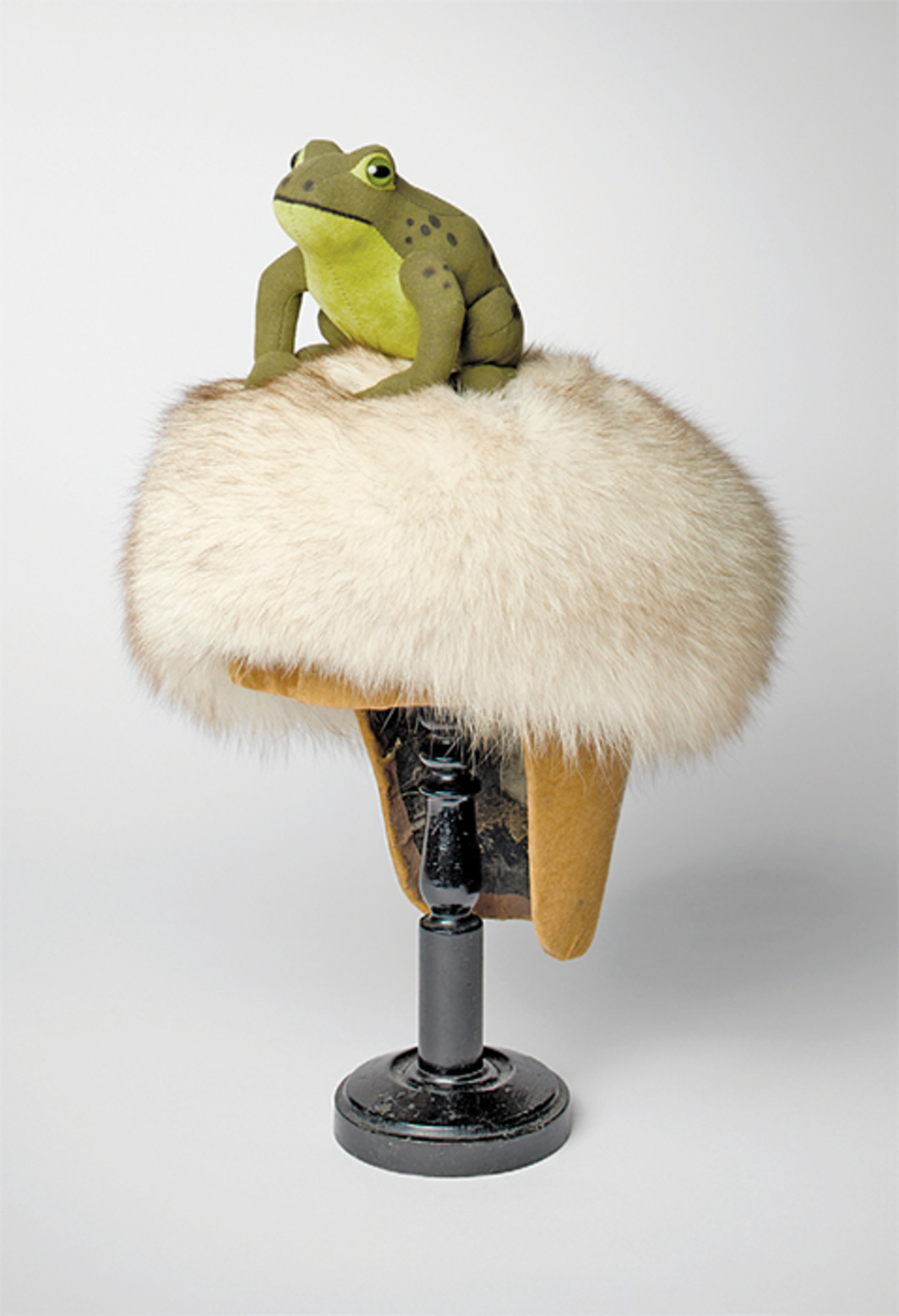 "Bethan Huws, Frog, 2011, wig stand, fur hat, toy frog, 17 × 11 × 11 3/4""."