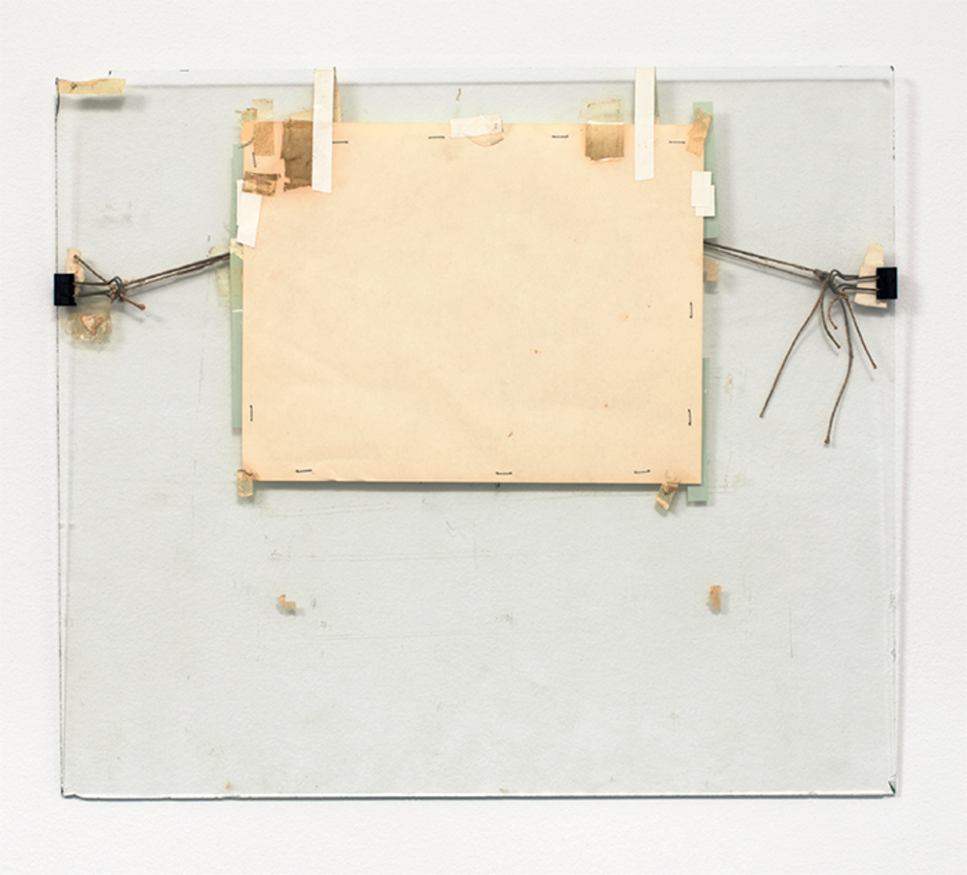 "Nahum Tevet, Untitled #5, 1972, paper, binder clips, twine, staples, plastic tape, masking tape, transparent tape, and wax pencil on glass, 17 1/4 × 19 3/4 × 1/2""."