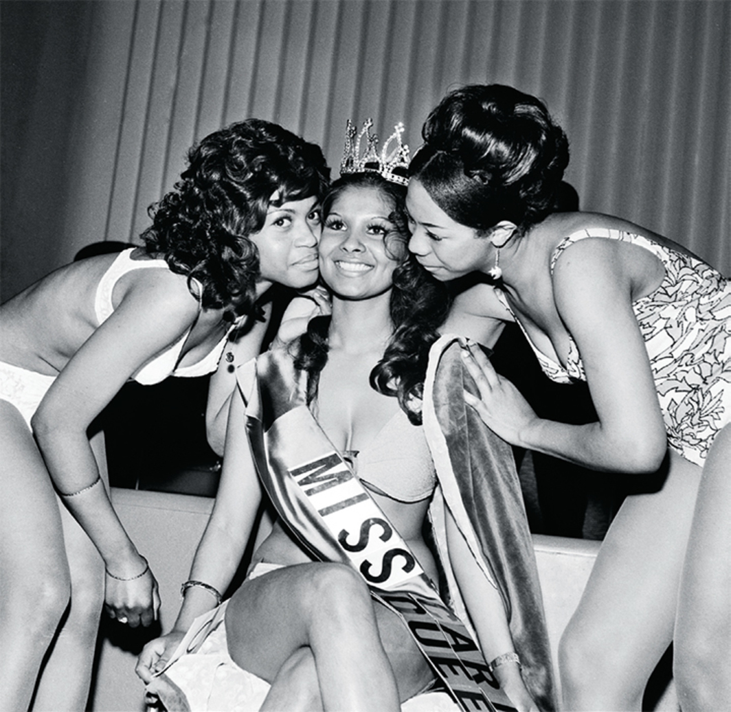 "Raphael Albert, Miss Caribbean Queen with fellow contestants, ca. 1970s, gelatin silver print, 30 × 30""."