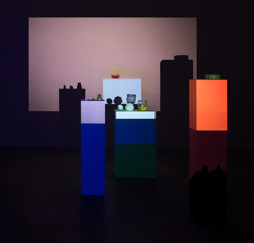 Lena Daly, Trix R,G,B, 2016, video and ultrasound projection, UV-reactive paint, wood pedestals, uranium glass, UV-reactive water, flock, HD projection, HSS speaker, LED UV light, dimensions variable.