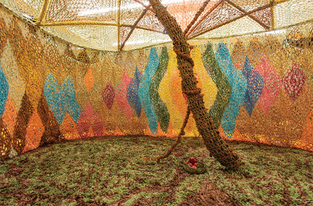 Ernesto Neto, The Serpent's energy gave birth to humanity, 2016, cotton voile crochet, cotton voile knot carpet, bamboo, semiprecious stones, wood, leaves, apples, guitar, bongos, maracas, dimensions variable.