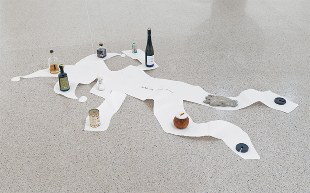 "Anna-Sophie Berger, Drunk or Dead?, 2016, paper, pencil, wine bottle, olive oil, whiskey, balsamic vinegar, canned beans, apricot jam, marzipan figurine, concrete hand, iron weights, salt, 13 × 90 1/2 × 47 1/4"". Photo: Klaus Pichler."