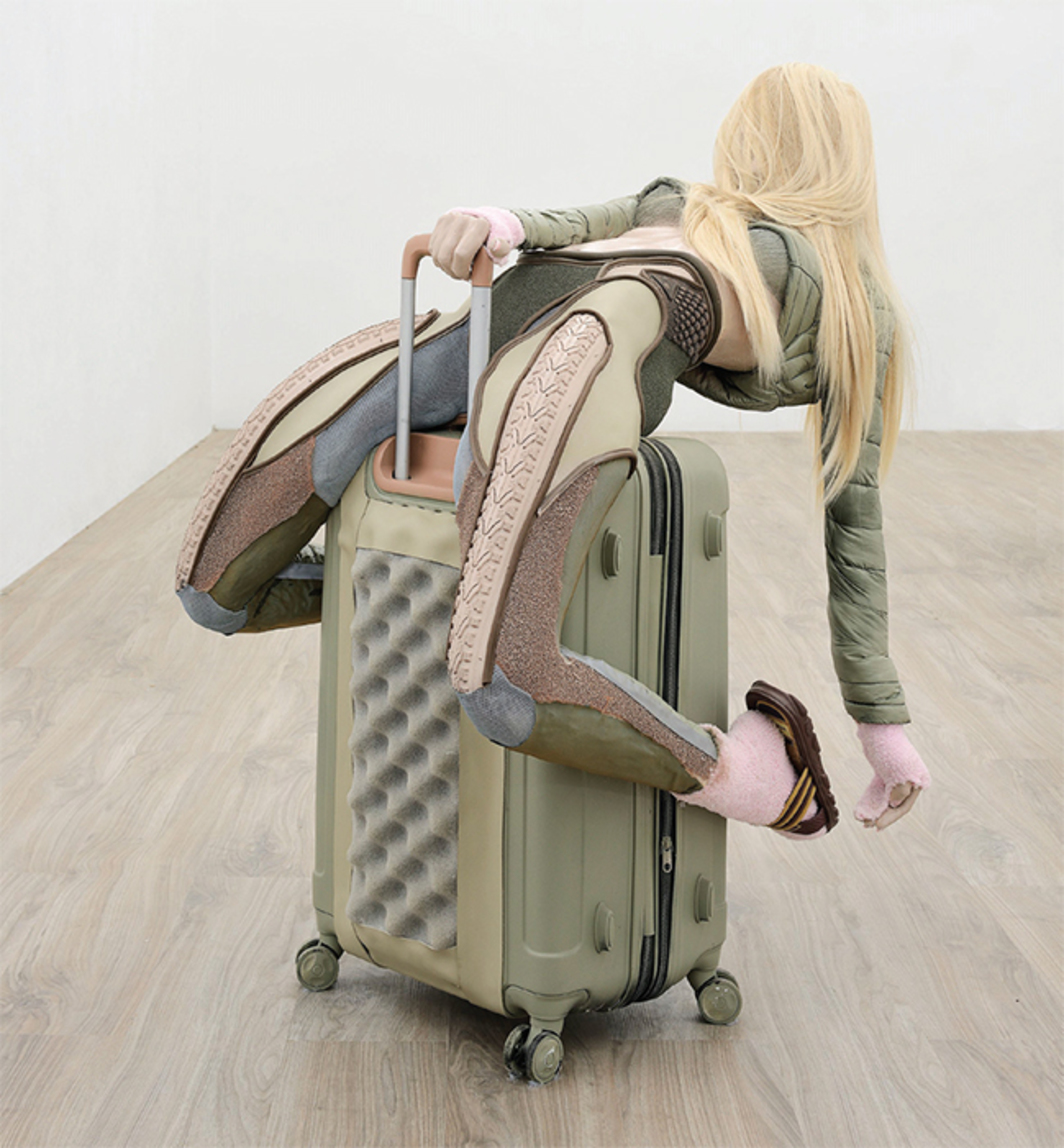 "Anna Uddenberg, Savage #9 (bea ride), 2017, aqua-resin, fiberglass, suitcase, puffy jacket, synthetic hair, acrylic nails, cozy socks, mesh, vinyl, rubber string, flip flops, 42 1/2 × 41 3/8 × 29 1/2"". From ""Homo Mundus Minor."" Photo: Roberto Apa."
