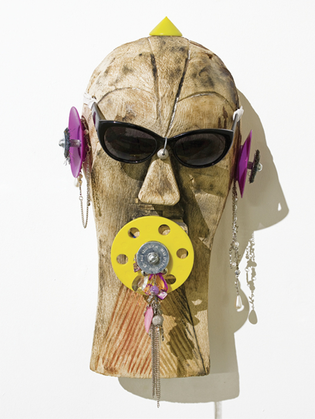 Pascale Marthine Tayou, Masque délavé (Faded Mask) (detail), 2015, mixed media on twenty-five wooden masks, dimensions variable.