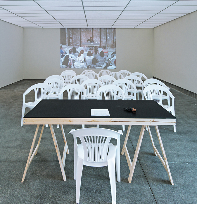 Tania Bruguera, Autosabotage (Self-Sabotage), 2009/2017, table, chairs, sound system, 38-mm firearm, video projection (color, sound, 12 minutes 9 seconds). Installation view. Photo: Charlie Villyard.