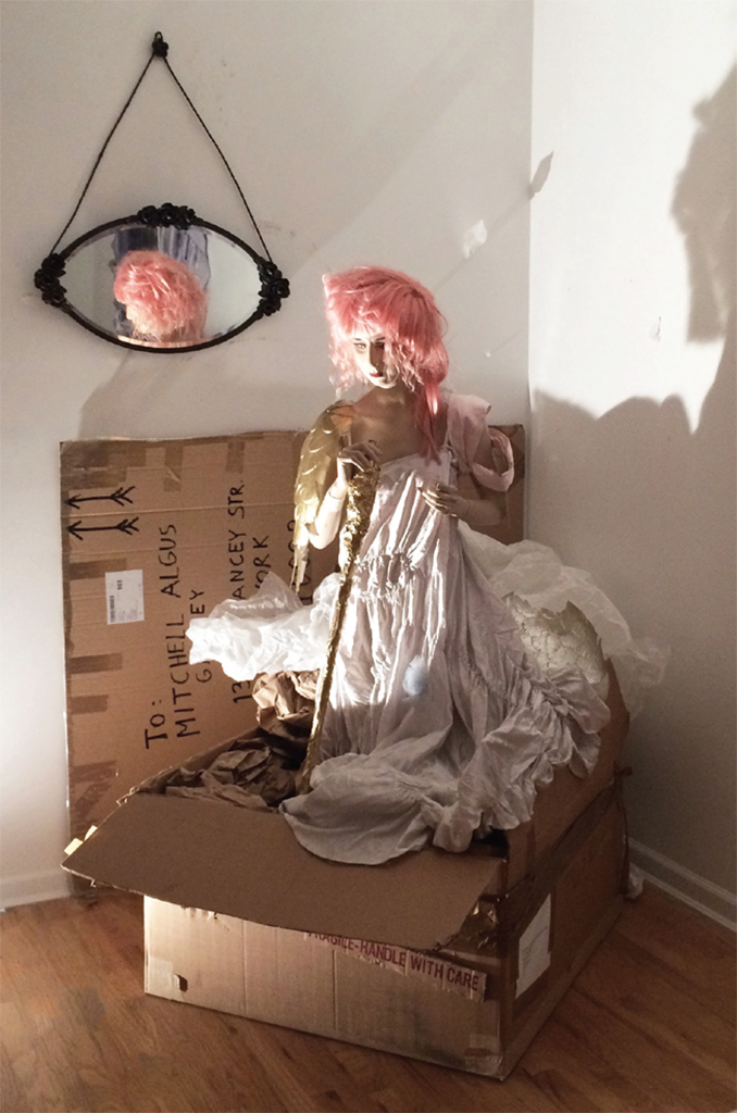 Colette, Arrived, 2017, mannequin, wig, fabric, packing materials, broom handle, aluminum foil, paint, vintage mirror, plastic angel wings. Installation view, Mitchell Algus Gallery, New York.