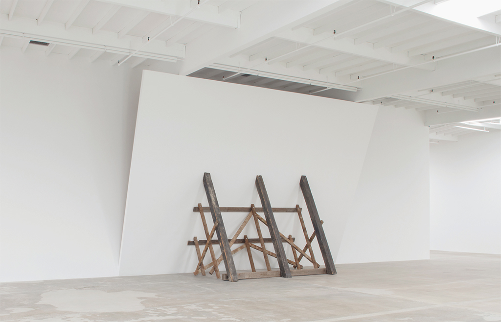 "David Lamelas, Untitled (Falling Wall), 1992–, drywall, wood, screws, acrylic paint, reclaimed lumber, 17' 5"" × 26' 8 1/2"" × 8' 1/2"". Photo: Josh White."