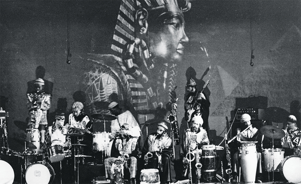 "Hartmut Geerken, Sun Ra Arkestra Performing at Heliopolis, Egypt, 1971, gelatin silver print, 5 x 7"". From ""Cosmic Communities: Coming Out into Outer Space—Homofuturism, Applied Psychedelia & Magic Connectivity."""