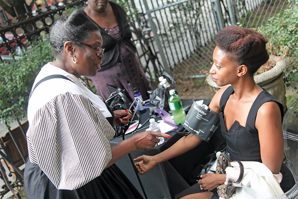 A member of the Black Nurses Association tests Nit Ra Sit's blood pressure at Simone Leigh's Free People's Medical Clinic, 2014, Stuyvesant Mansion, Brooklyn, New York, September 20, 2014. Photo: Shulamit Seidler-Feller.