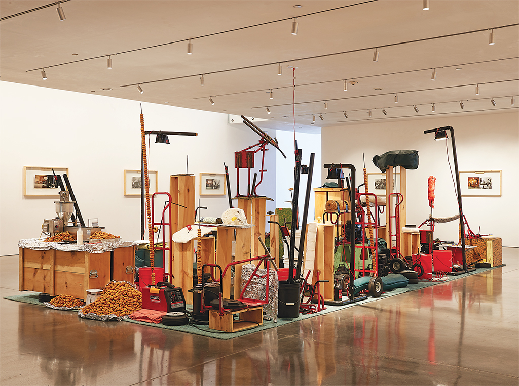 Jason Rhoades, My Brother/Brancuzi, 1995, carpet, wood, steel, small gasoline engines, tools, plastic, doughnut machine, mixed media. Installation view, 2017–18. Photo: Laura Wilson. © The Estate of Jason Rhoades.