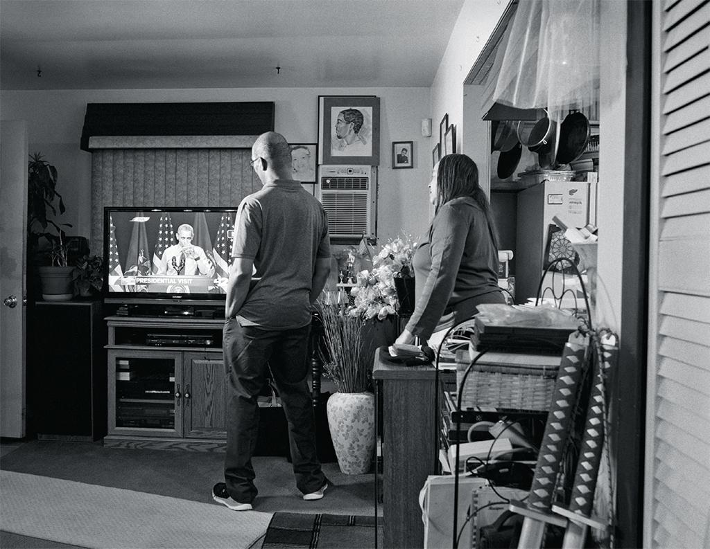 "LaToya Ruby Frazier, Shea's Aunt Denise and Uncle Rodney in their home on Foster Street watching President Barack Obama take a sip of Flint water, 2016–17, gelatin silver print, 20 x 24""."