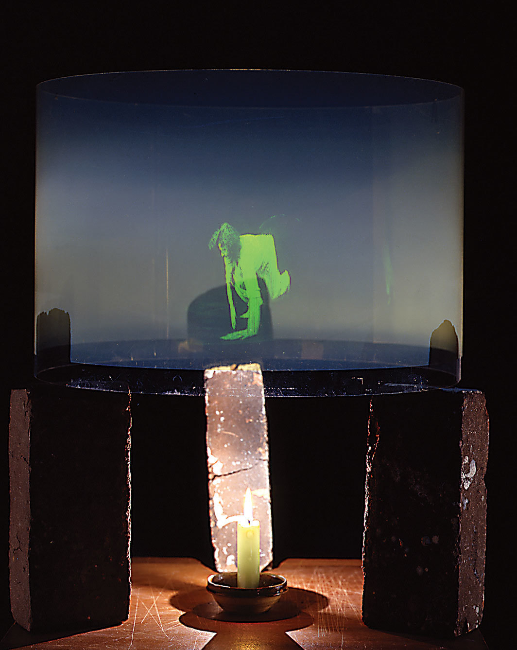 "Simone Forti, Striding Crawling, 1977, holographic film, Plexiglas, polymer protective covering, candle, candle dish, bricks, 25 × 18 × 18""."