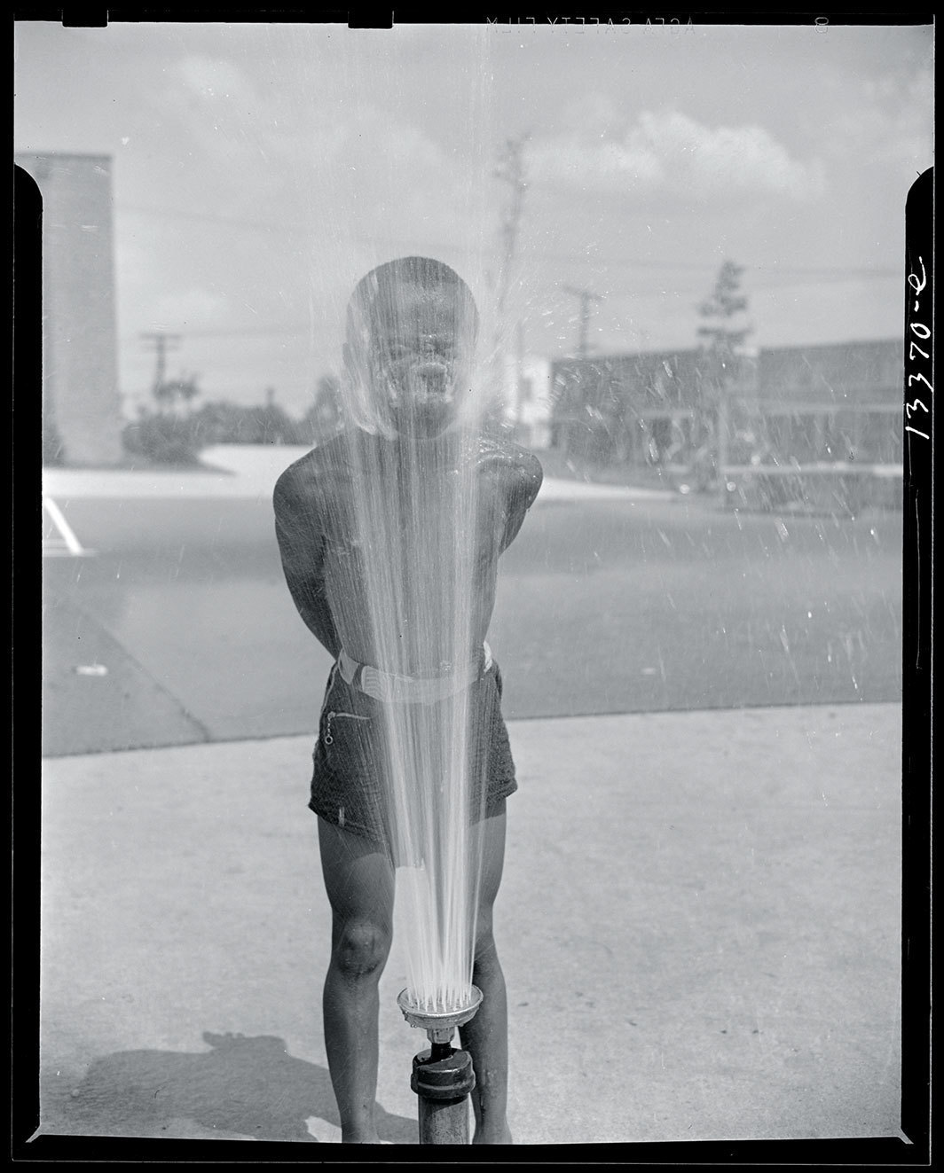 Gordon Parks, Playing in  the community sprayer, Frederick Douglass housing project, Anacostia, Washington, D.C., June 1942. Credit Library of Congress, Prints & Photographs Division, FSA/OWI Collection.