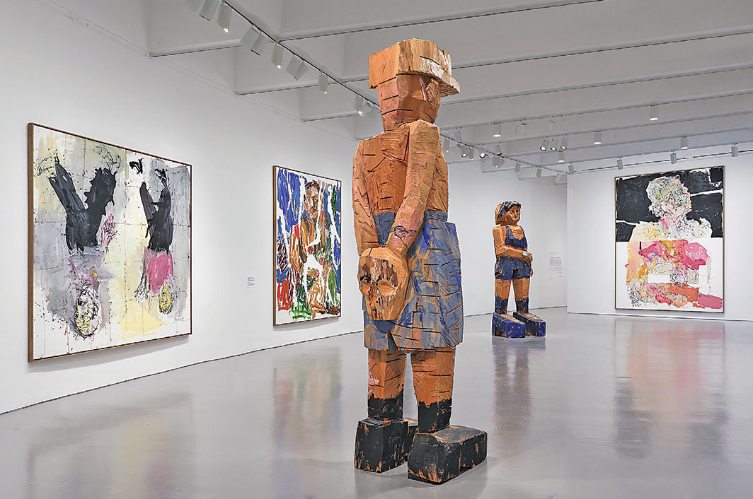 "View of ""Baselitz: Six Decades,"" 2018. Floor: Meine neue Mütze (My New Hat), 2003; Frau Ultramarin (Mrs. Ultramarine), 2004.  Wall, from left: Adieu (Remix), 2006; Ein Grüner kaputt '67 (Remix) (A Green One Kaput '67 [Remix]), 2007; Beginging, 2011."