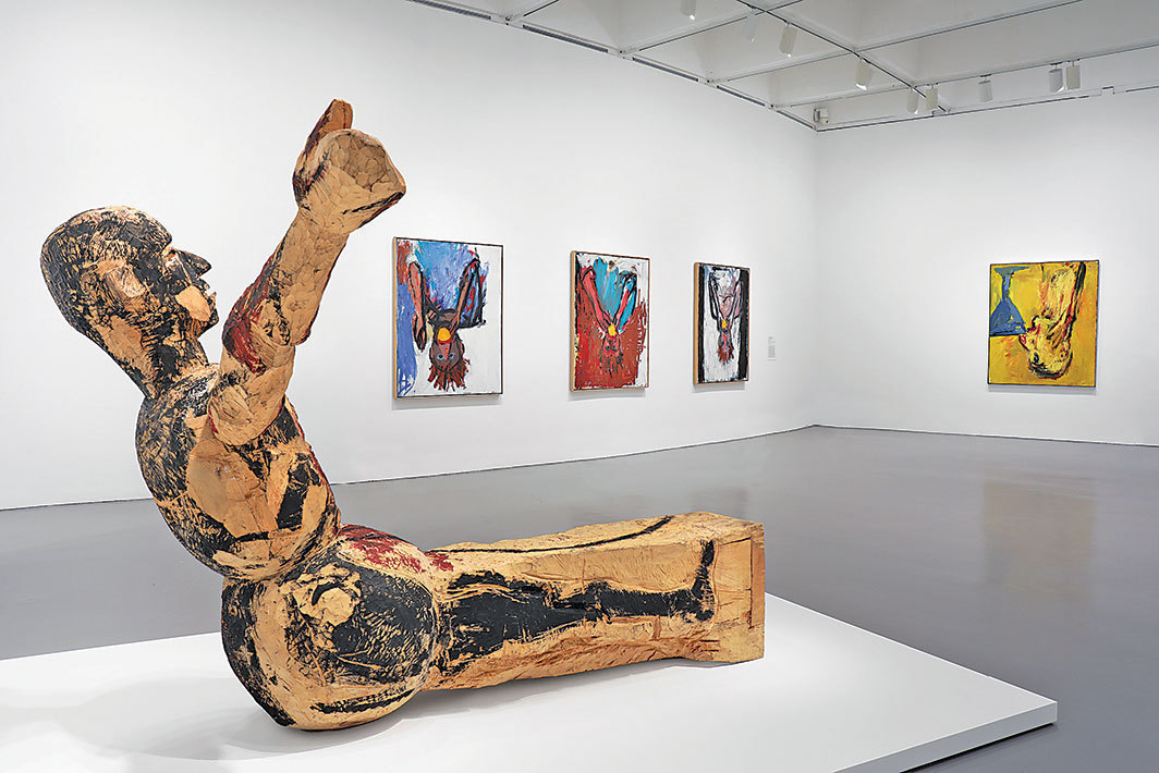 "View of ""Baselitz: Six Decades,"" 2018. Floor: Modell für eine Skulptur (Model for a Sculpture), 1979–80. Wall, from left: Orangenesser (IX) (Orange Eater [IX]), 1981; Orangenesser VI (Orange Eater VI), 1981; Orangenesser I (Orange Eater I), 1981; Orangenesser VI (Orange Eater VI), 1981."