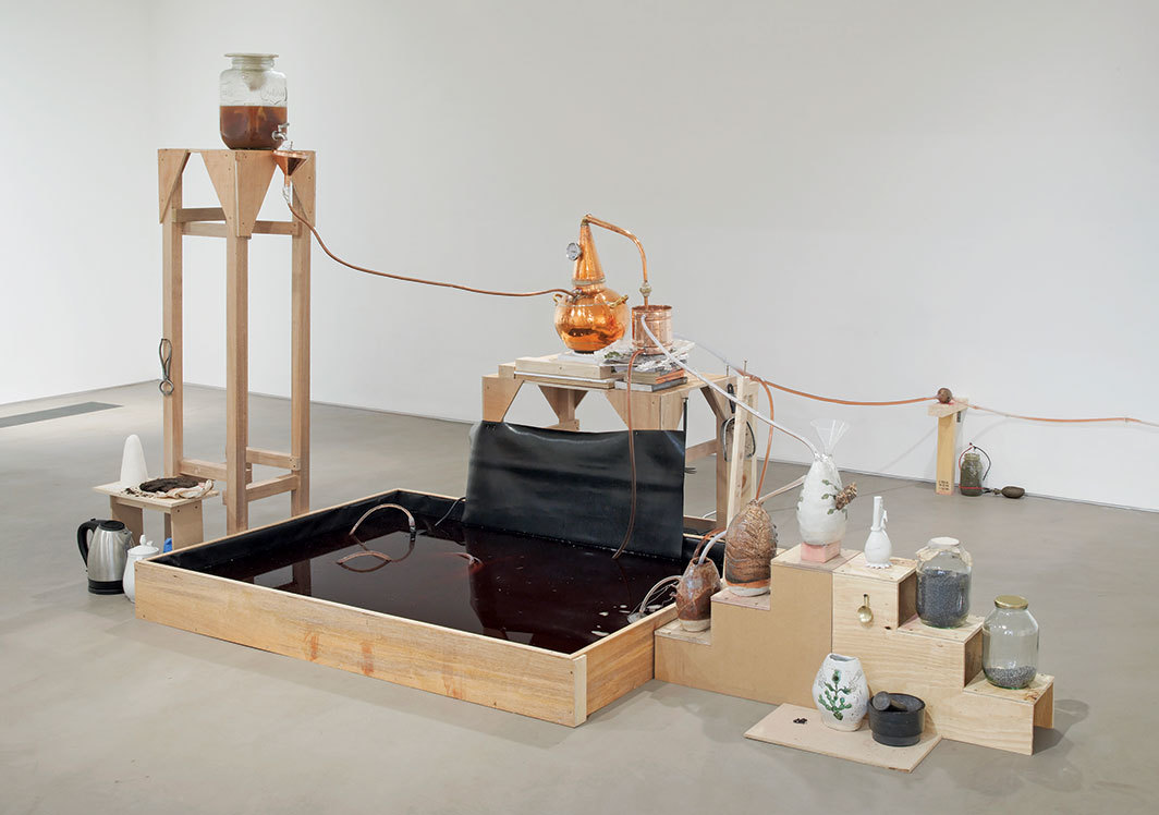 Candice Lin, System for a Stain, 2016, wood, glass jars, cochineal, poppy seeds, metal castings, water, tea, sugar, copper still, hot plate, ceramic, mortar and pestle, mud, microbial mud battery, vinyl. Installation view, Gasworks, London. Photo: Andy Keate.
