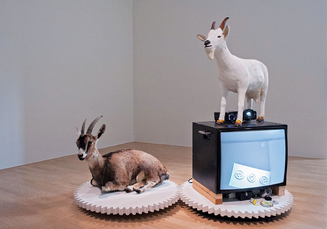 Stephan Dillemuth, Ziegenkarussell (Goat Carousel), 2012/2018, monitor, surveil- lance camera, video projector, motor, plaster, taxidermied goats, plastic. Installation view, Lenbachhaus, Munich, 2018.