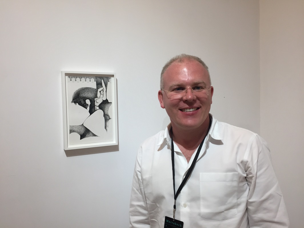 Dealer Toby Clarke with a drawing by Ibrahim El-Salahi.