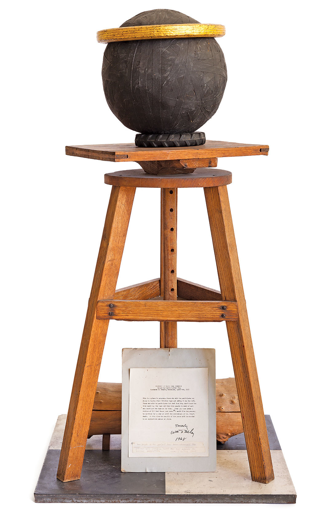 "William T. Wiley, Movement to Blackball Violence (Homage to Martin Luther King), 1968, black friction tape, wooden stool, gold leaf, rubber tricycle tires, carved wooden log by H. C. Westermann, paper and tape on board, linoleum flooring, 50 × 24 × 24""."