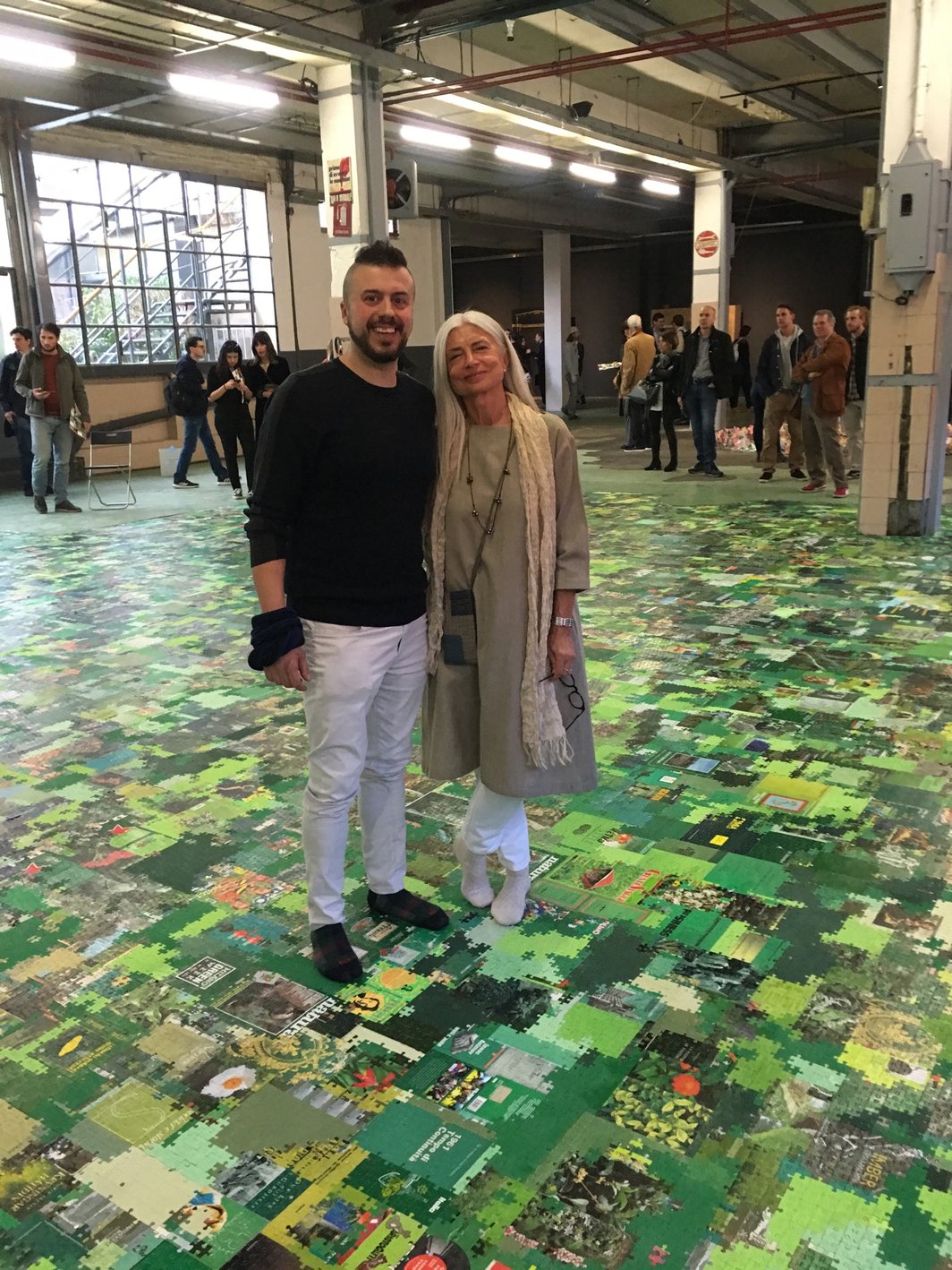 Artist Andrea Mastrovito with curator Elena Quarestani, standing on Matrovito's installation, Babel, 2019.