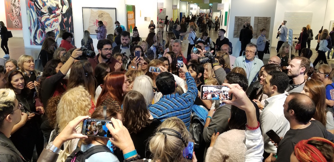 A crowd gathers to take selfies with Marta Minujín after her guided tour at arteBA.