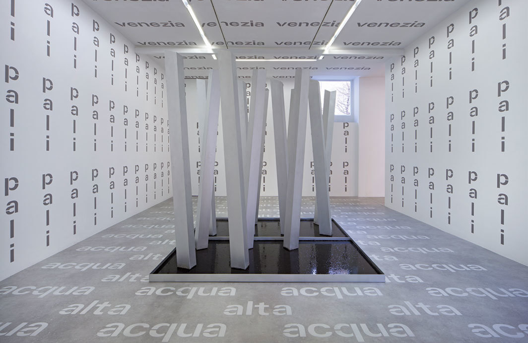Gina Pane, Acqua alta/Pali/Venezia (High Water/Piles/Venice), 1968–70/2019, twelve Duralinox pillars, metal tray, muddy water, painted lettering. Installation view.