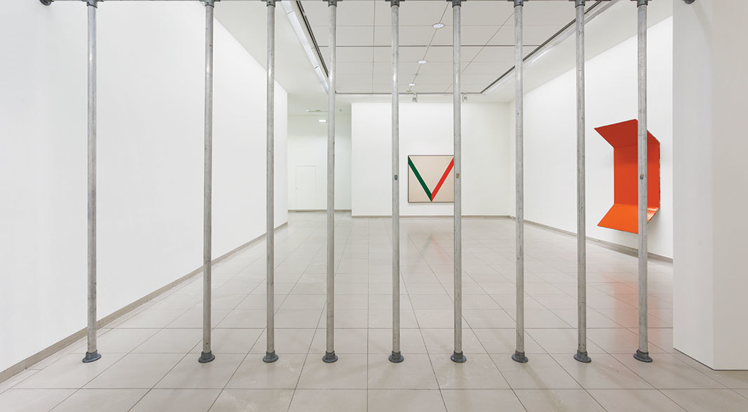 "View of ""Cady Noland,"" 2018–19. Foreground: Cady Noland, Dead Space, 1989. Background, from left: Kenneth C. Noland, Touch, 1963; Steven Parrino, Bent Painting, 1991. Photo: Axel Schneider."