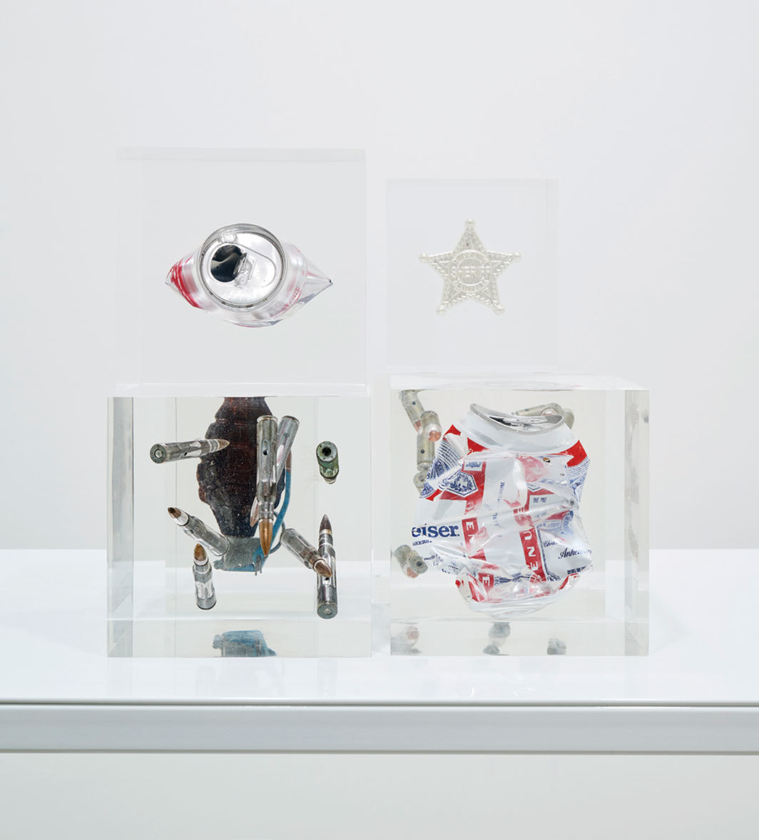 "Cady Noland, Untitled, 1986–2018, bullets, hand grenade, Coca-Cola can, beer can, sheriff badge, Plexiglas, overall 11 × 11 3⁄8 × 9 3⁄4""."