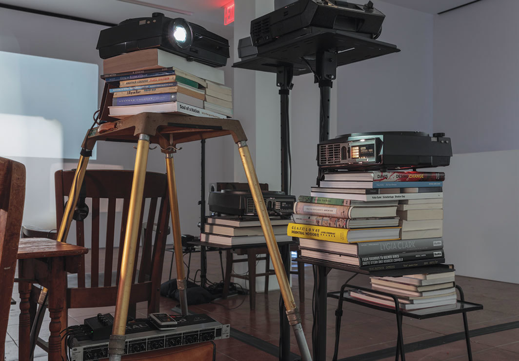 Andrea Geyer, Feeding the Ghost, 2019, slide projectors, projector stands, books, sandbags, furniture, lamps, 60-minute voice-over. Installation view.