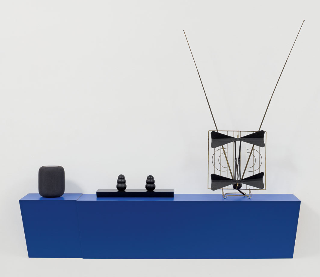 "Haim Steinbach, Untitled (siri, kongs, antenna), 2019. Plastic-laminated wood shelf, Apple smart speaker, rubber dog chew, indoor television antenna, 53 × 58 1⁄2 × 12""."