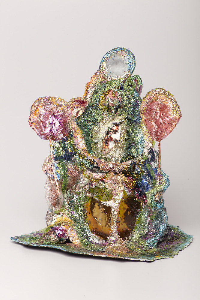 "Thomas Lanigan-Schmidt, The Mirror of Youth (Spritzer Thaw), 1970–72, aluminum foil, plastic wrap, pipe cleaner, holographic tape, pipe cleaners, glitter, staples, mirror, colored marker, 13 x 10 x 9""."