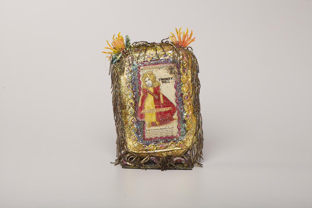 "Thomas Lanigan-Schmidt, Twinky as a Royal Princess (Self-Portrait), 1967, foil, printed material, linoleum, glitter, staples, Magic Marker, found objects and other media, 10 x 7 1/2 x 4 1/2""."