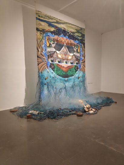 Waylon James D'Souza, The Cascade of Futures Past: Journey Through the Eocene and Speculations on the Post-silicon Age, 2019, mixed-media installation comprising a print on sustainable produced hemp fabric, salvaged ghost nets, gill nets, beach debris (plastics), oyster shells and other mollusks, 108 x 60''.