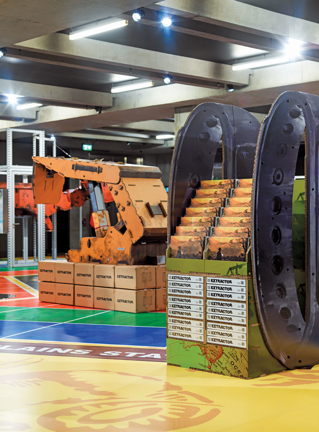 "View of ""Simon Denny: Mine,"" 2019–20, Museum of Old and New Art, Hobart, Australia. From left: Caterpillar Inc. semi-autonomous longwall coal mining roof support system cardboard display, 2019; Caterpillar Biometric worker fatigue monitoring smartband Extractor pop display, 2019. Photo: Jesse Hunniford."