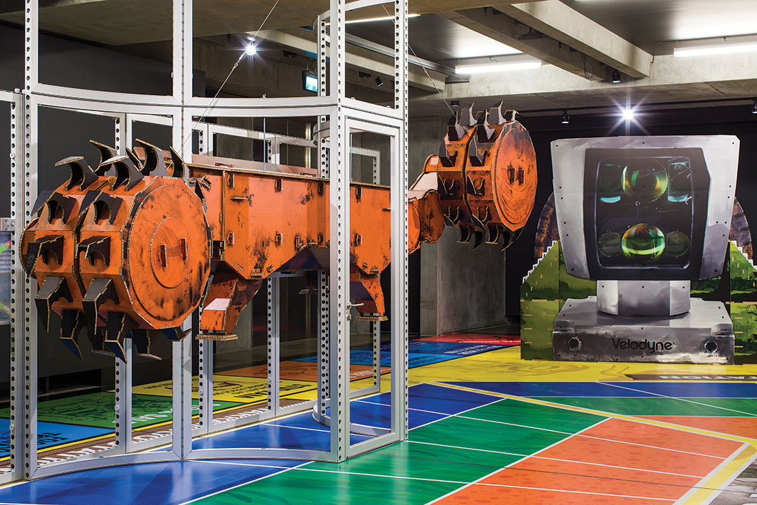 "View of ""Simon Denny: Mine,"" 2019–20, Museum of Old and New Art, Hobart, Australia. From left: Joy Global semi-autonomous longwall coal mining 7LS8  shearer cardboard display, 2019; Caterpillar Inc. Autonomous  haul 793F Mining Truck Extractor pop display, 2019. Photo: Jesse Hunniford."