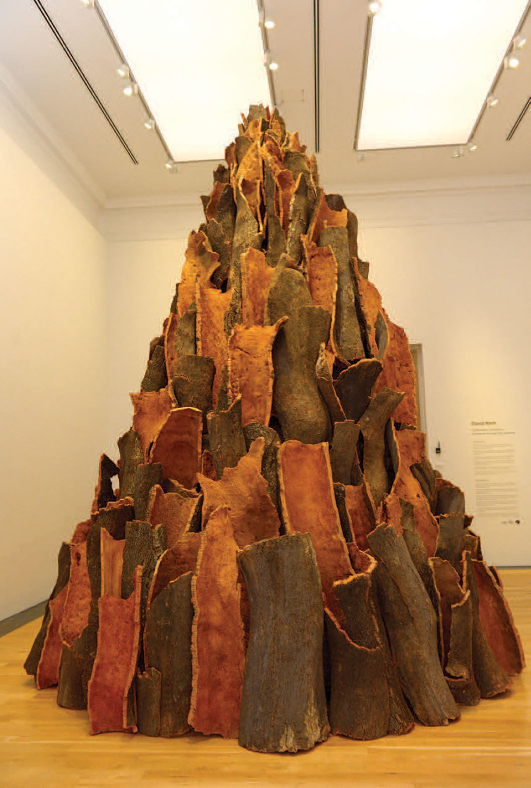 "David Nash, Cork Spire, 2012, cork bark, 17' 3 1⁄8"" × 13' 11 3⁄8"" × 13' 11 3⁄8""."