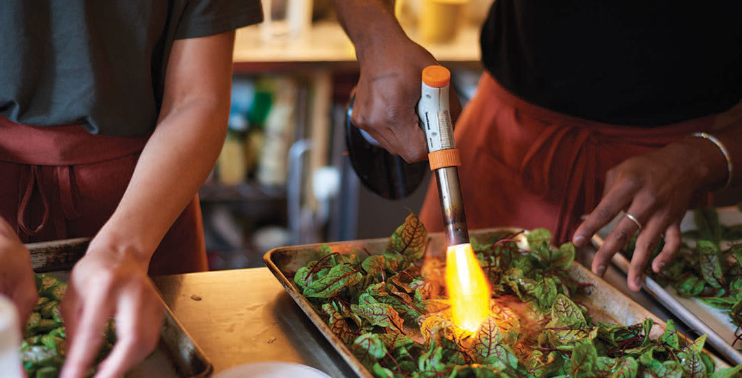 "Imani Elizabeth Jackson and S*an D. Henry-Smith torching sorrel for fried oyster cakes at ""The Pearl Diver's Revenge,"" Bar Laika, Brooklyn, June 4, 2019. Photo: Danny Sadiel Peña."