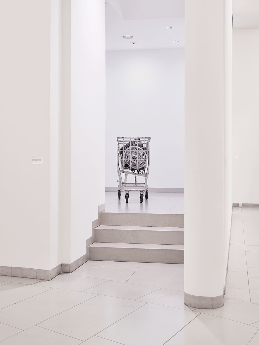 Cady Noland, Cart Full of Action, 1986, metal cart, rims, rear-view mirror, exhaust, engine oil, battery charger, various plastics, oil-based car care products. Installation view, Museum für Moderne Kunst, Frankfurt, 2018. Photo: Fabian Frinzel.