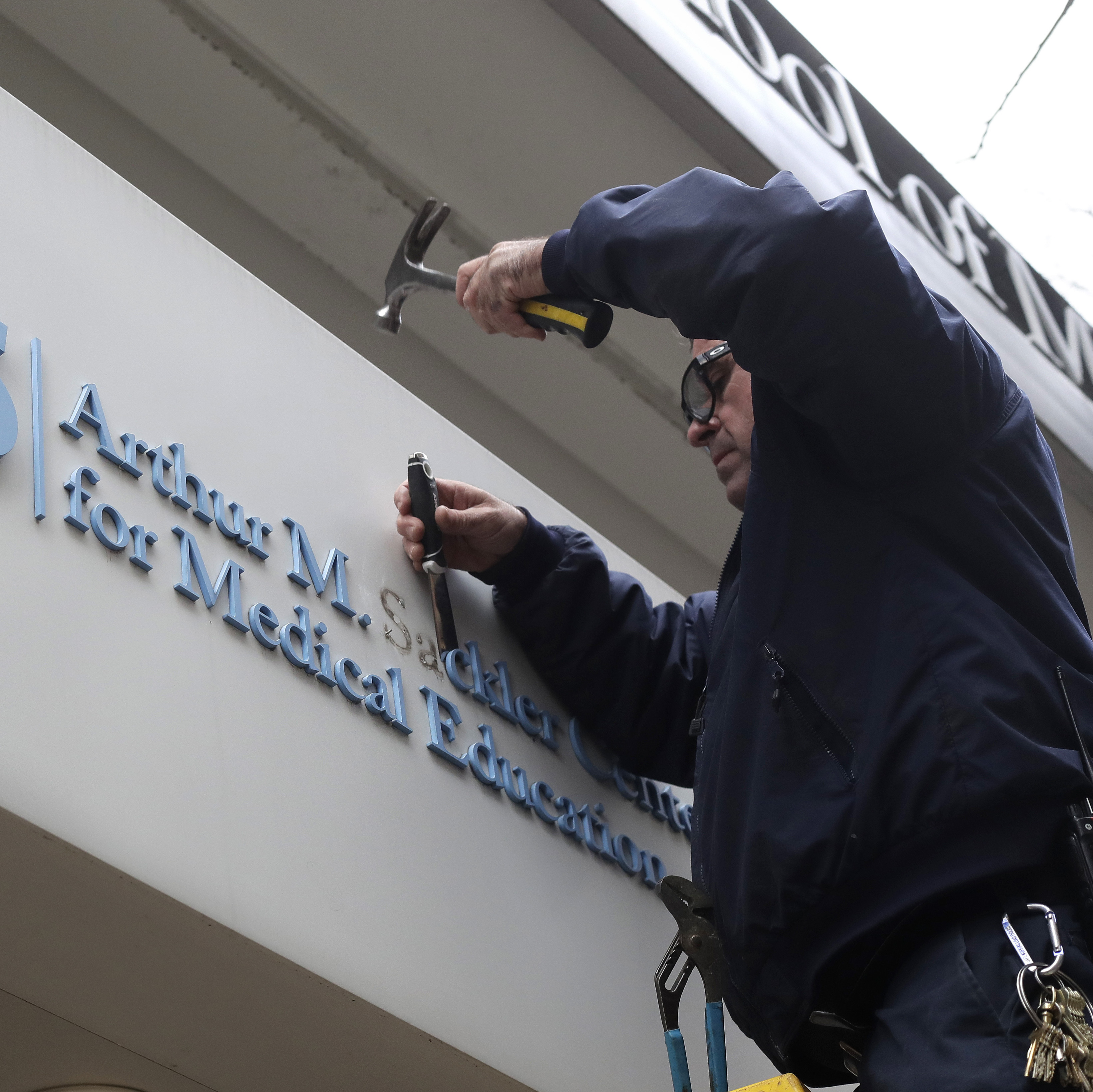 Worker Gabe Ryan removes a sign that includes the name Arthur M. Sackler at an entrance to Tufts School of Medicine, on Thursday, Dec. 5, 2019. Photo: AP/Steven Senne.