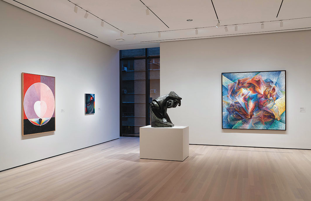 "View of ""Circa 1913,"" 2019–, Museum of Modern Art, New York. From left: Hilma af Klint, The Dove, no. 2, Series UW, Group IX, 1915; Georgia O'Keeffe, Lake George, Coat and Red, 1919; Raymond Duchamp-Villon, The Horse, 1914; Umberto Boccioni, Dynamism of a Soccer Player, 1913. Photo: Jonathan Muzikar."