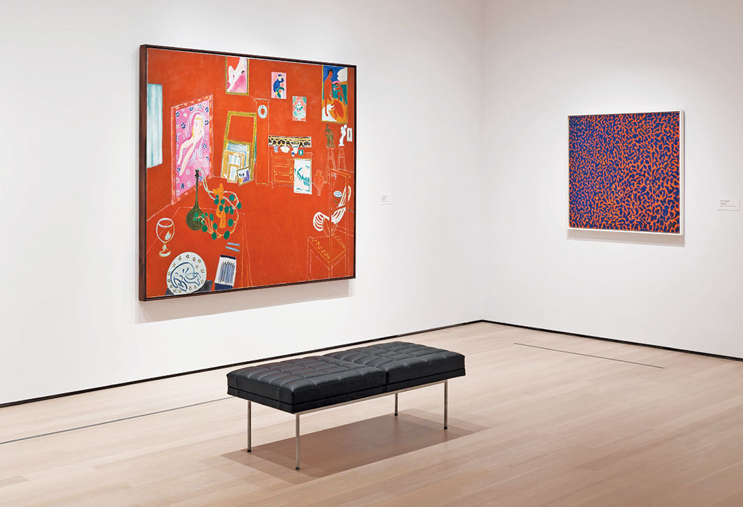 "View of ""Henri Matisse,"" 2019–, Museum of Modern Art, New York. From left: Henri Matisse, The Red Studio, 1911; Alma Thomas, Fiery Sunset, 1973. Photo: Jonathan Muzikar."