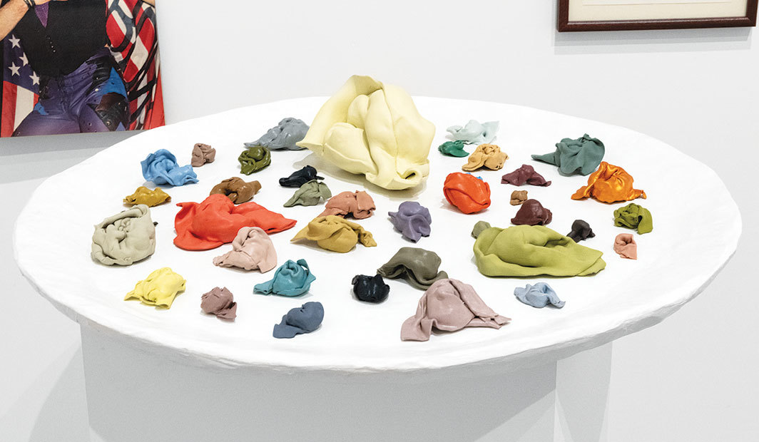 "Rachel Harrison, 1:1 (Wonton: John) (detail), 1996, thirty-eight pictures of Johns, thirty-eight unfired clay and polymer clay wontons, overall 8'1 1⁄4"" × 13' 11 3⁄4"" × 46""."