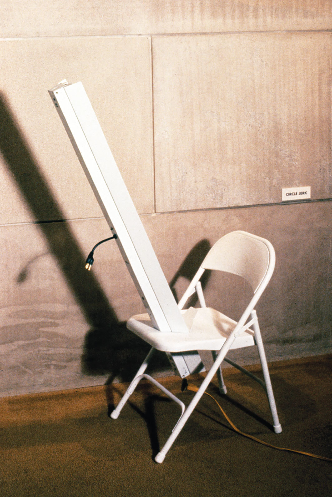 Rachel Harrison, Circle Jerk, 1989, metal folding chair, fluorescent light, extension cord, wood, motor, paintbrush, electrical box, wiring, light switch, metallic paint on canvas, dimensions variable.